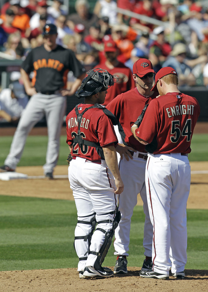 Photo -   Arizona Diamondbacks pitching coach Charles Nagy, middle, talks with pitcher Barry Enright and Miguel Montero during the third inning of a spring training baseball game against the San Francisco Giants, Sunday, March 4, 2012, in Scottsdale, Ariz. (AP Photo/Darron Cummings)