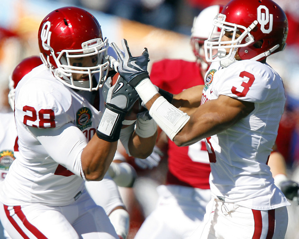 Oklahoma's Travis Lewis (28) pulls in an interception in front of teammate Jonathan Nelson (3) during the first half of the Brut Sun Bowl college football game between the University of Oklahoma Sooners (OU) and the Stanford University Cardinal on Thursday, Dec. 31, 2009, in El Paso, Tex.   Photo by Chris Landsberger, The Oklahoman