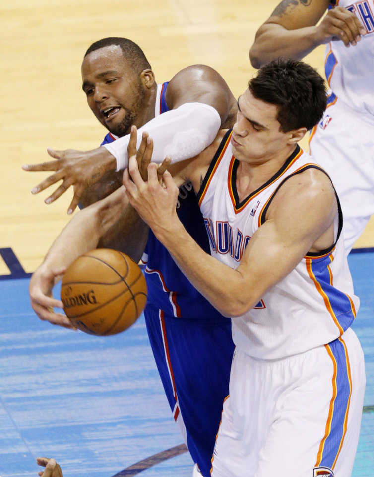 Photo - Steven Adams (12) battles Glen Davis (0) fight for a loose ball during Game 5 of the Western Conference semifinals in the NBA playoffs between the Oklahoma City Thunder and the Los Angeles Clippers at Chesapeake Energy Arena in Oklahoma City,  Tuesday, May 13, 2014. Photo by Bryan Terry, The Oklahoman