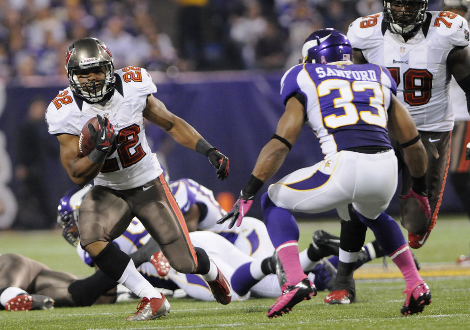 Photo -   Tampa Bay Buccaneers running back Doug Martin, left, runs from Minnesota Vikings strong safety Jamarca Sanford during the first half of an NFL football game Thursday, Oct. 25, 2012, in Minneapolis. (AP Photo/Jim Mone)