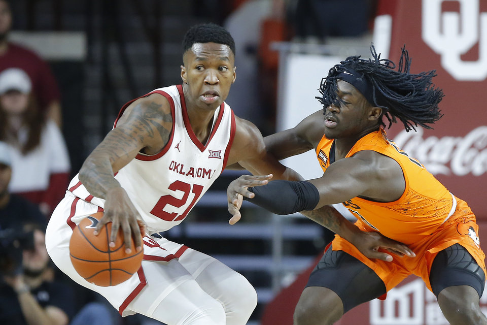 Photo - Oklahoma's Kristian Doolittle (21) goes past Oklahoma State's Isaac Likekele (13) during a Bedlam college basketball game between the University Oklahoma Sooners (OU) and the Oklahoma State Cowboys (OSU) at the Lloyd Noble Center in Norman, Okla., Saturday, Feb. 1, 2020. Oklahoma won 82-69. [Bryan Terry/The Oklahoman]