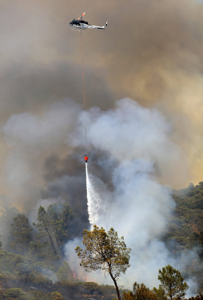 Photo - A private hire helicopter makes water drop on the Butts Fire above Butts Canyon Road as the afternoon winds kicked up, Wednesday, July 2, 2014, near Pope Valley in Napa County, Calif. (AP Photo/Santa Rosa Press Democrat, Kent Porter)
