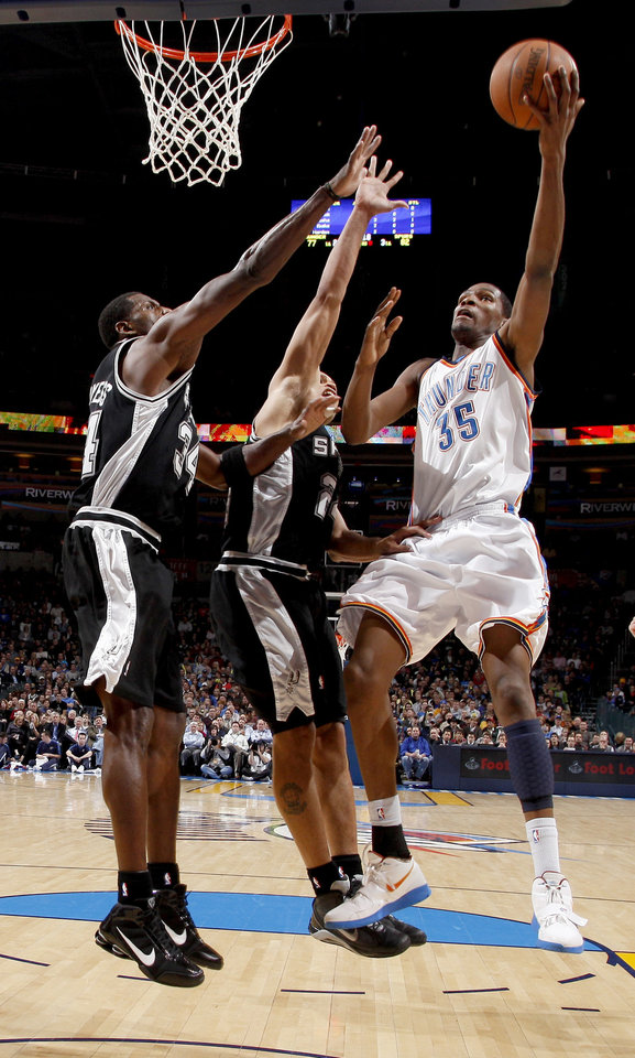 Oklahoma City's Kevin Durant moves to the basket beside Antonio McDyess, left, and Richard Jefferson during the NBA basketball game between the Oklahoma City Thunder and the San Antonio Spurs at the Ford Center in Oklahoma City, Wednesday, January 13, 2010. Photo by Bryan Terry, The Oklahoman