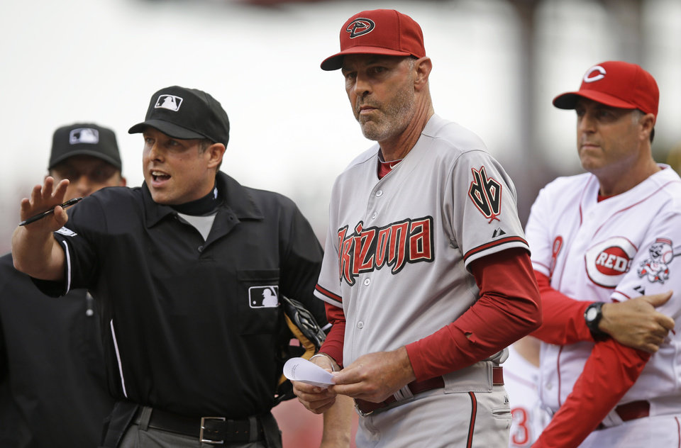 Photo - Arizona Diamondbacks manager Kirk Gibson, center, and Cincinnati Reds manager Bryan Price, right, listen to home plate umpire Hal Gibson go over the ground rules prior to a baseball game, Monday, July 28, 2014, in Cincinnati. (AP Photo/Al Behrman)