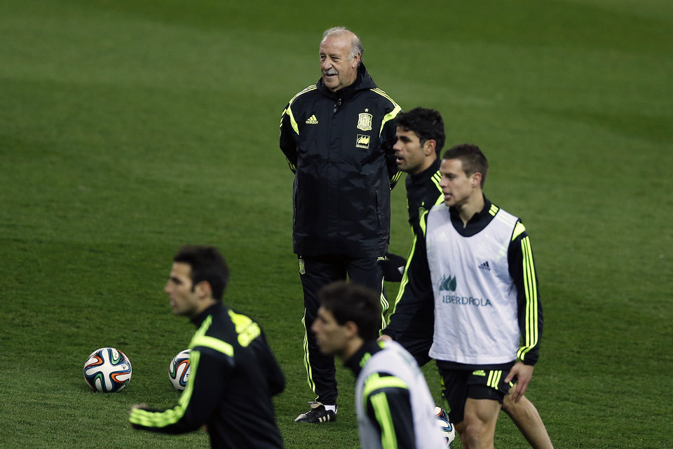 Photo - Spain's coach Vicente del Bosque, top, watches his players Diego Costa, center left, during a training session in Madrid, Spain, Tuesday March 4, 2014. Spain will play Italy in a friendly soccer match on Wednesday. (AP Photo/Andres Kudacki)