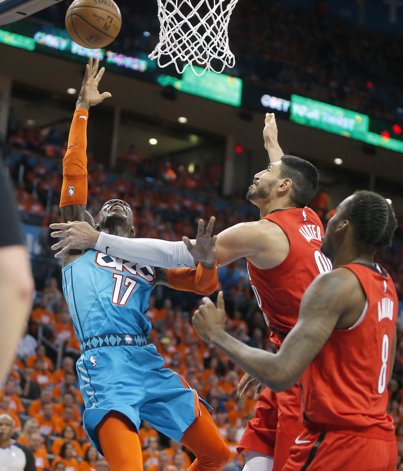 Photo - Oklahoma City's Dennis Schroder (17) is fouled by Portland's Enes Kanter (00) during Game 3 in the first round of the NBA playoffs between the Portland Trail Blazers and the Oklahoma City Thunder at Chesapeake Energy Arena in Oklahoma City, Friday, April 19, 2019. Oklahoma City won 120-108. Photo by Bryan Terry, The Oklahoman