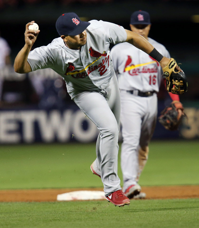 Photo - St. Louis Cardinals' Jhonny Peralta throws to first for an out on Philadelphia Phillies Marlon Byrd in the eighth inning of a baseball game, Friday, Aug. 22, 2014, in Philadelphia. Phillies won 5-4. (AP Photo/Laurence Kesterson)