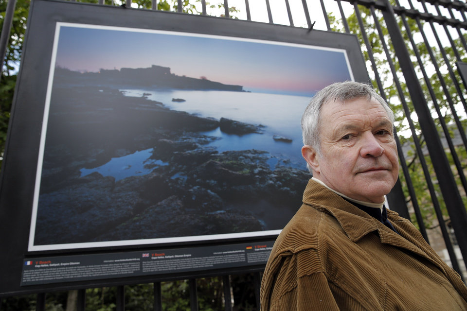 Photo - British photographer Michael St Maur Sheil poses in front of one of his pictures displayed at the Paris Luxembourg gardens, Tuesday, April 8, 2014, as part of an exhibition