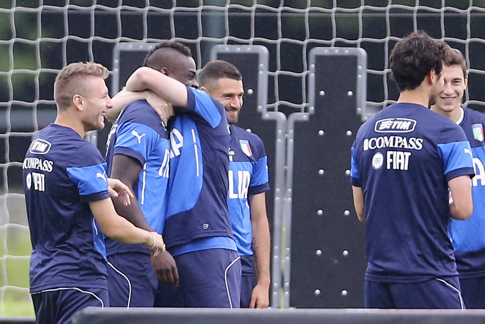 Photo - Italy's Mario Balotelli, second from left, is embraced by his teammate Ignazio Abate, during a training session in Mangaratiba, Brazil, Tuesday, June 10, 2014.  Flanking them are a smiling Ciro Immobile, left, and Antonio Candreva. Italy will play in group D of the Brazil 2014 soccer World Cup. (AP Photo/Antonio Calanni)