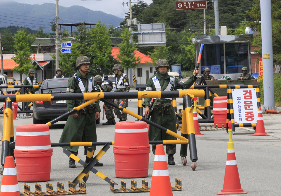 Photo - South Korean army soldiers stand guard on the road to search for a South Korean conscript soldier who is on the run after a shooting incident at a temporary checkpoint  in Goseong, South Korea, Sunday, June 22, 2014.  The military searched Sunday for an armed South Korean soldier who fled after killing five of his comrades and wounding seven at an outpost near the North Korean border.(AP Photo/Ahn Young-joon)