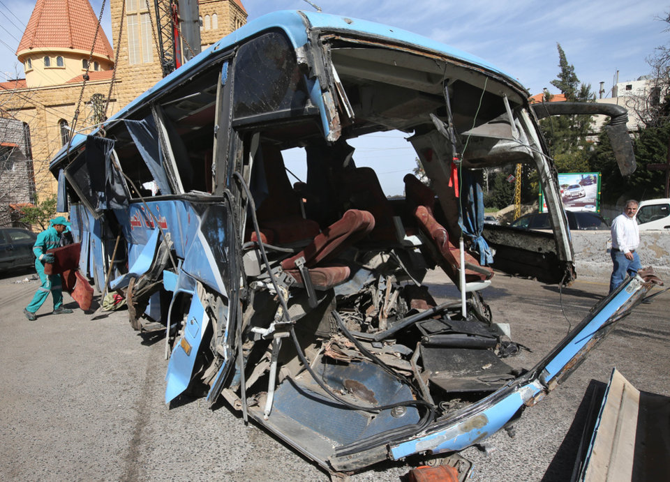 Photo - A worker, left, removes a damaged seat from a destroyed Syrian bus that was headed to the Lebanese capital, Beirut, when an accident occurred in the Kahhaleh region of Lebanon, Friday March 15, 2013. Officials say at least eight Syrians were killed and 29 were injured when the bus they were traveling in from Syria overturned in the mountains in central Lebanon. (AP Photo/Hussein Malla)