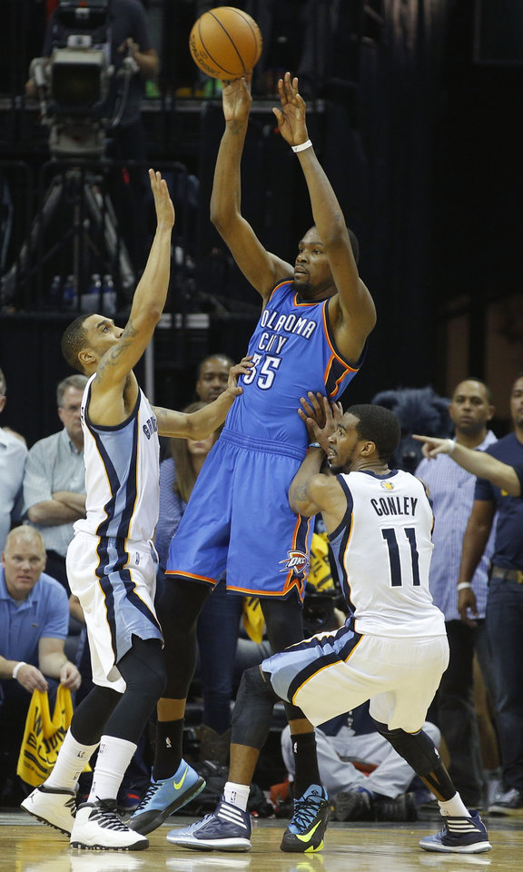 Photo - Oklahoma City's Kevin Durant (35) passes the ball from between Memphis' Courtney Lee (5) and Mike Conley (11) during Game 4 in the first round of the NBA playoffs between the Oklahoma City Thunder and the Memphis Grizzlies at FedExForum in Memphis, Tenn., Saturday, April 26, 2014. Photo by Bryan Terry, The Oklahoman