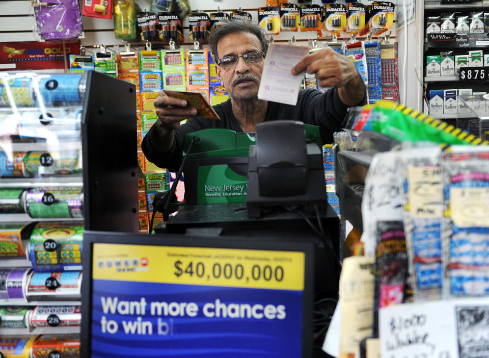 Photo - Baiju Amin hands lottery tickets to a customer at Union Food Store in Totowa, N.J. on Sunday, March 24, 2013. The lone winning ticket for a $338.3 million Powerball drawing was sold in New Jersey. Details on where and when the winning ticket was purchased and other related information were not disclosed Sunday by New Jersey Lottery officials, who also would not say if anyone claiming to hold the ticket had contacted them as of Sunday afternoon. (AP Photo/The Record (Bergen County NJ), Tyson Trish)