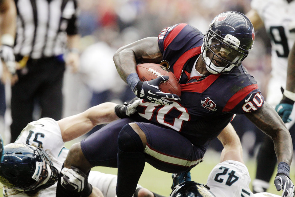 Photo -   Houston Texans wide receiver Andre Johnson (80) is tackled by Jacksonville Jaguars Paul Posluszny (51) and Chris Prosinski (42) during the fourth quarter of an NFL football game, Sunday, Nov. 18, 2012, in Houston. (AP Photo/Patric Schneider)