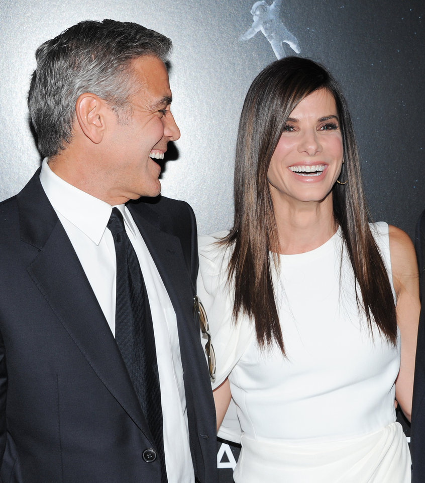 "Photo - Actors George Clooney and Sandra Bullock share a laugh together at the premiere of ""Gravity"" at the AMC Lincoln Square Theaters on Tuesday, Oct. 1, 2013, in New York. (Photo by Evan Agostini/Invision/AP) ORG XMIT: NYEA128"