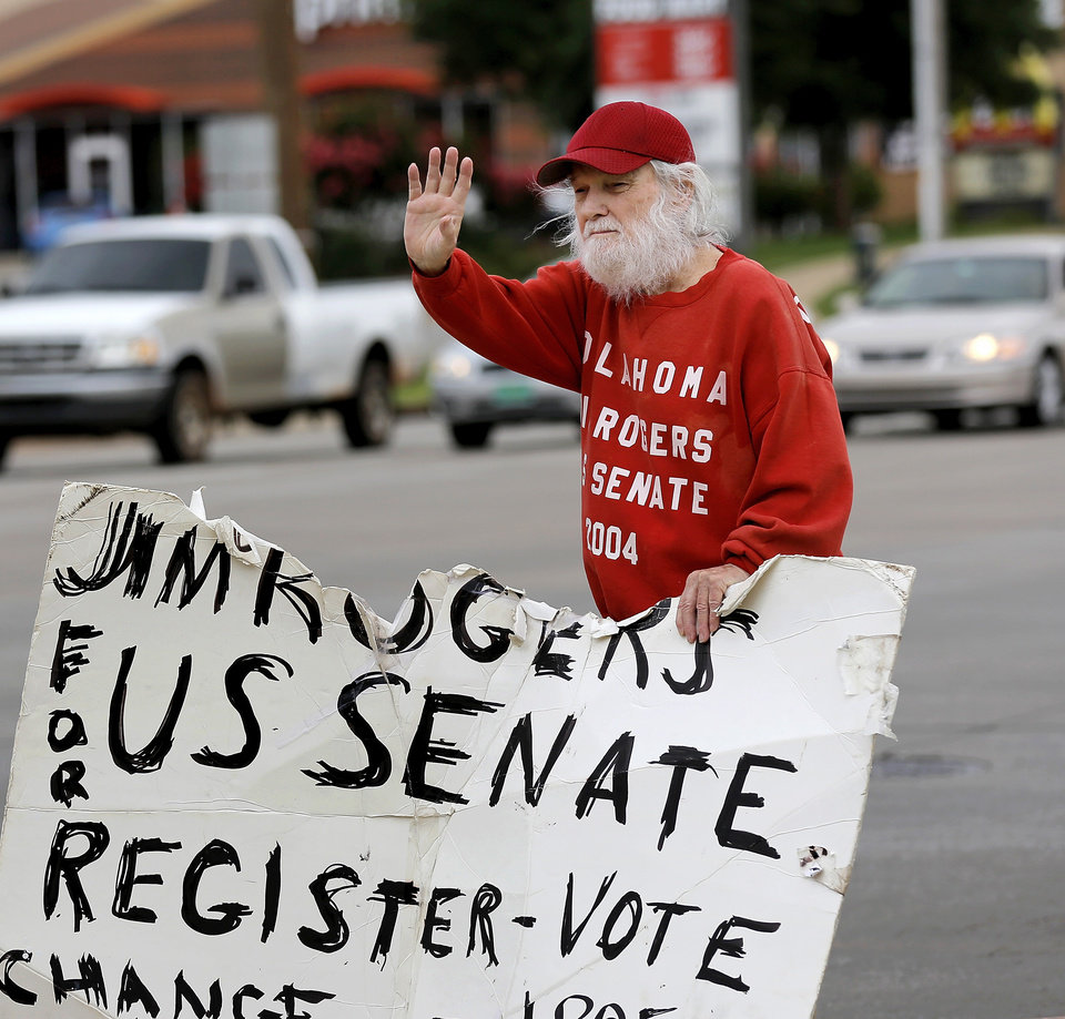 Photo -  U.S. Senate candidate Jim Rogers waves to passing cars at an intersection in Midwest City as he holds up one of his handmade campaign signs June 26. Photo by Jim Beckel, The Oklahoman   Jim Beckel -