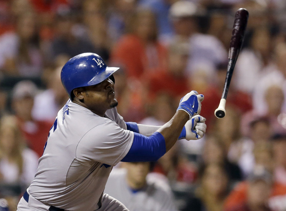Photo - Los Angeles Dodgers' Juan Uribe loses his bat as he pops out in foul territory to St. Louis Cardinals catcher Tony Cruz to end the top of the eighth inning of a baseball game Friday, July 18, 2014, in St. Louis. (AP Photo/Jeff Roberson)