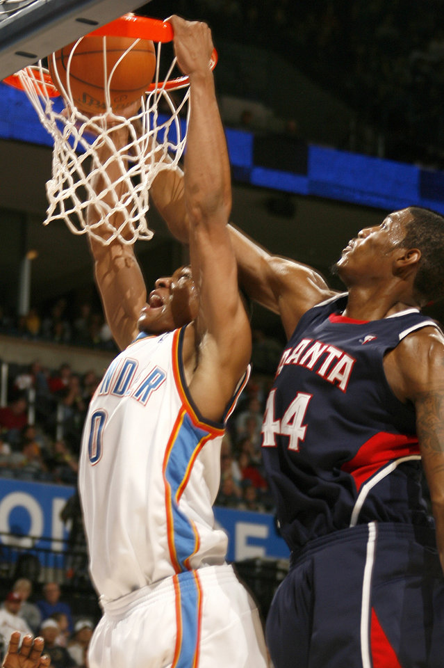 Photo - Oklahoma City's Russell Westbrook (0) dunks as Atlanta's Solomon Jones (40 defends during the second half of the NBA game between Oklahoma City Thunder and the Atlanta Hawks, Sunday, Nov. 9, 2008, at  the Ford Center, Oklahoma City. PHOTO BY SARAH PHIPPS, THE OKLAHOMAN