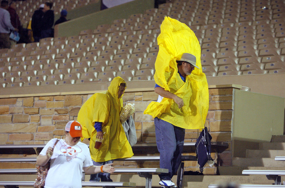 Photo - Fans leave during a rain delay before the Oklahoma State-Tulsa game on Saturday in Tulsa. Photo by Sarah Phipps, The Oklahoman
