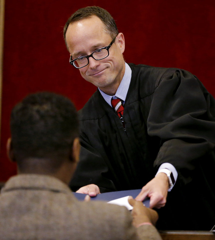 Photo -  Special Judge Michael Tupper hands out graduation certificates Thursday. [Photo by Steve Sisney, The Oklahoman]