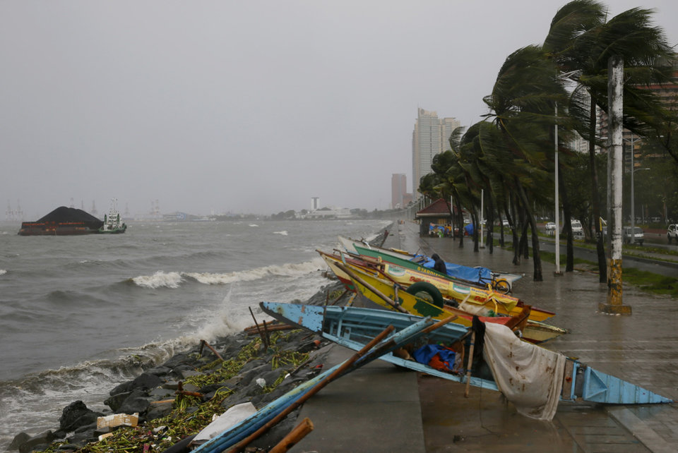Photo - Small fishing boats are placed by the seawall as strong winds and slight rain brought by Typhoon Koppu hit Manila, Philippines Sunday, Oct. 18, 2015. The slow-moving typhoon blew ashore with fierce wind in the northeastern Philippines early Sunday, toppling trees and knocking out power and communications. Officials said there were no immediate reports of casualties. (AP Photo/Bullit Marquez)