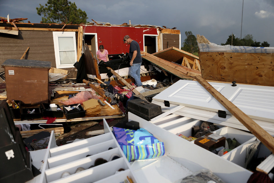 Photo - Nancy and Jason Townsend sort through belongings after their home was hit by a tornado in Carney Okla., on Sunday, May 19, 2013. The Townsend's left their home to avoid the tornado. (AP Photo/The Oklahoman, Bryan Terry)