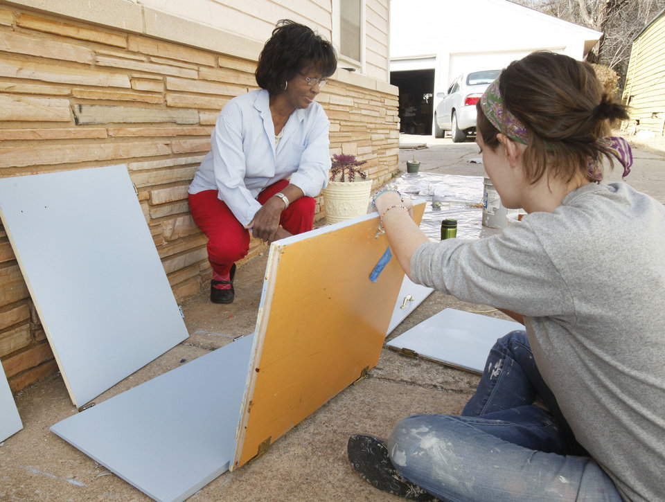 Eunice Russell watches Sara Constantineau repaint cabinet doors at her home at 2521 NE 14th St. in Oklahoma City during Rebuilding Together. Photo By Paul Hellstern, The Oklahoman <strong>PAUL HELLSTERN - Oklahoman</strong>