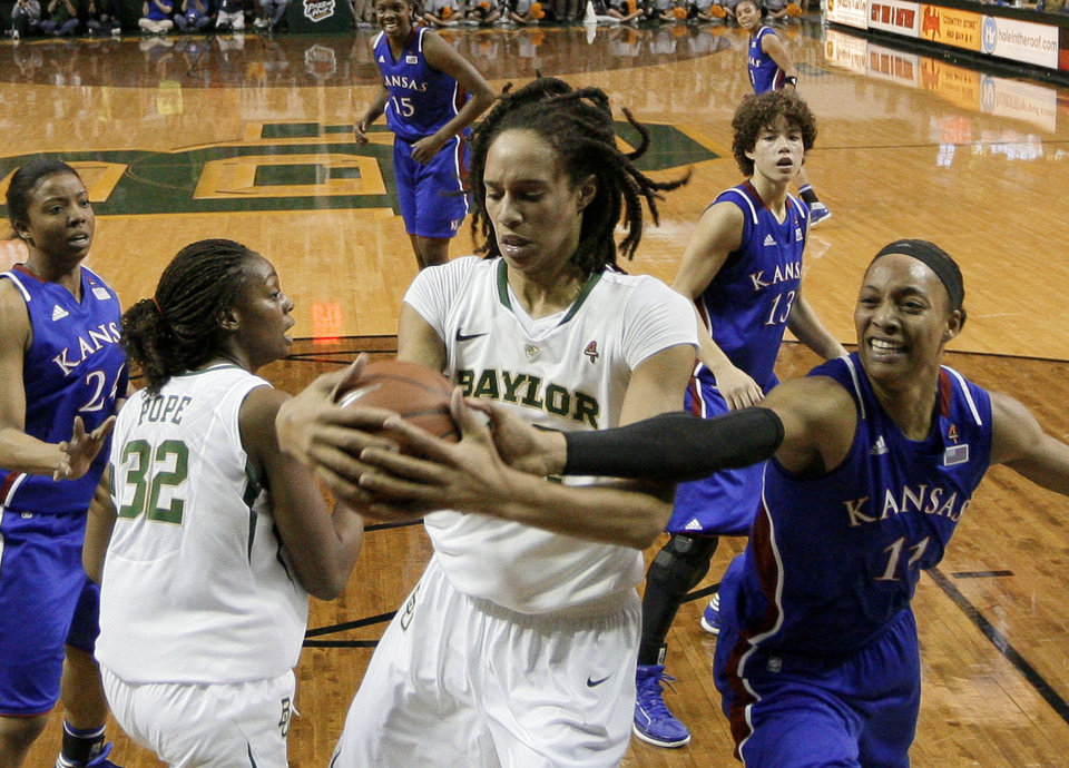 Photo -   Baylor center Brittney Griner, center, grabs a rebound against Kansas 's Aishah Sutherland (11) in the first half of an NCAA women's college basketball game Saturday, Jan. 28, 2012, in Waco, Texas. Griner had seven rebounds, five blocks and 28-points in the 74-46 Baylor win. (AP Photo/Tony Gutierrez)