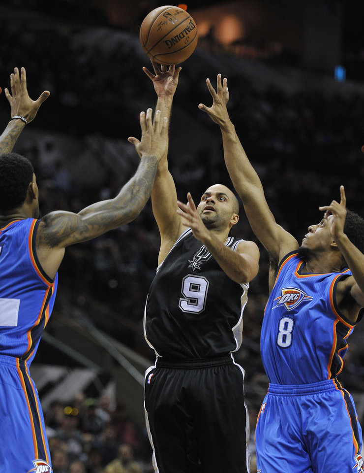 Photo - San Antonio Spurs guard Tony Parker, center, of France, shoots against Oklahoma City Thunder guard Ish Smith, right, and Thunder forward Mitch McGary, during the first half an NBA basketball game, Dec. 25, 2014, in San Antonio. (AP Photo/Darren Abate)