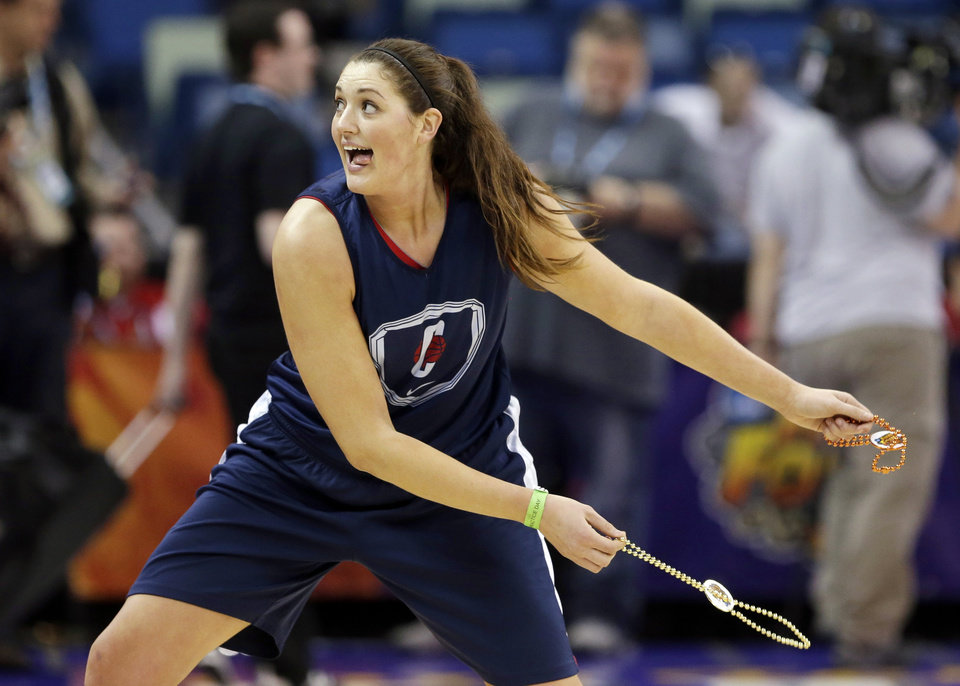 Photo - Connecticut center Stefanie Dolson throws Mardi Gras beads to the fans during practice at the Women's Final Four of the NCAA college basketball tournament, Saturday, April 6, 2013, in New Orleans.  UConn plays Notre Dame in a semifinal game on Sunday. (AP Photo/Gerald Herbert)