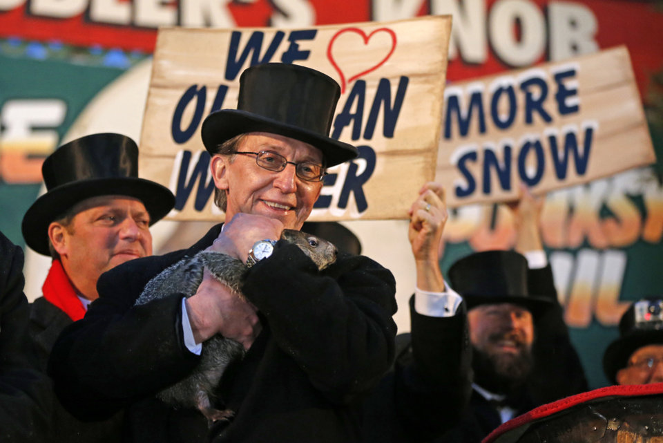 Photo - Punxsutawney Phil is held by Ron Ploucha after emerging from his burrow Sunday, Feb. 2, 2014, on Gobblers Knob in Punxsutawney, Pa., to see his shadow and forecast six more weeks of winter weather. The prediction this year fell on the same day as Super Bowl Sunday.  (AP Photo/Gene J. Puskar)