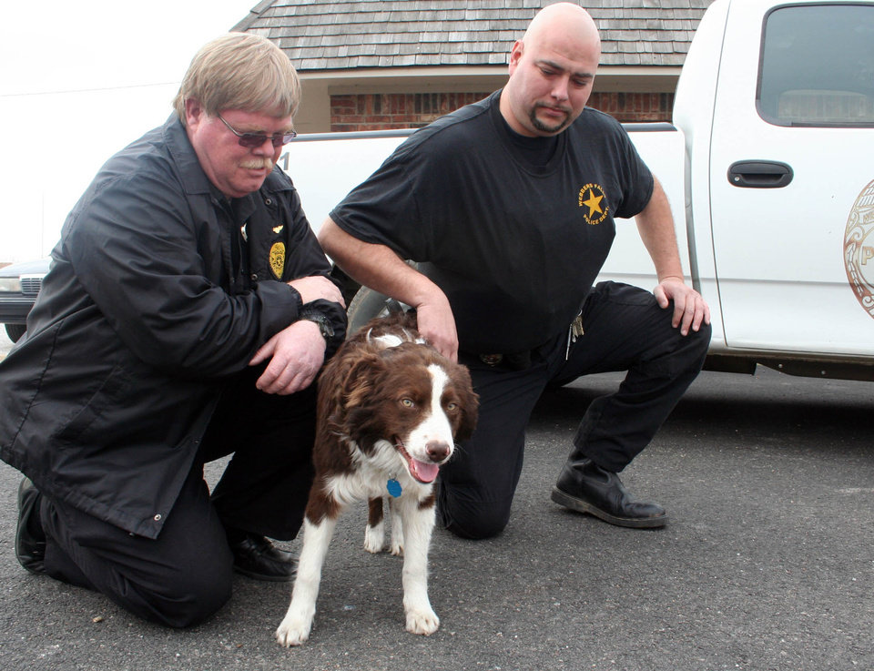 Photo - DOG RESCUE: Webbers Falls Police Chief Tim Brown (blondish hair) and Officer Mark Adney (black shirt) is fond of the town's newly adopted dog