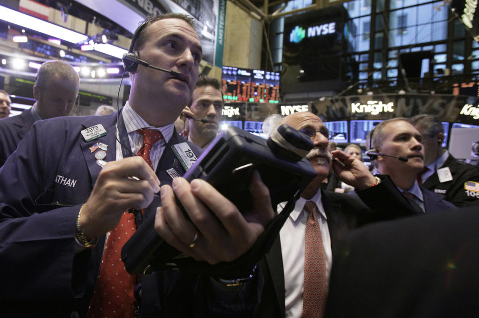 Photo -   Jonathan Corpina, left, works with fellow traders on the floor of the New York Stock Exchange Friday, Oct. 5, 2012. Stocks are rising in early trading on Wall Street after the government reported that the U.S. unemployment rate fell below 8 percent for the first time in almost four years. (AP Photo/Richard Drew)