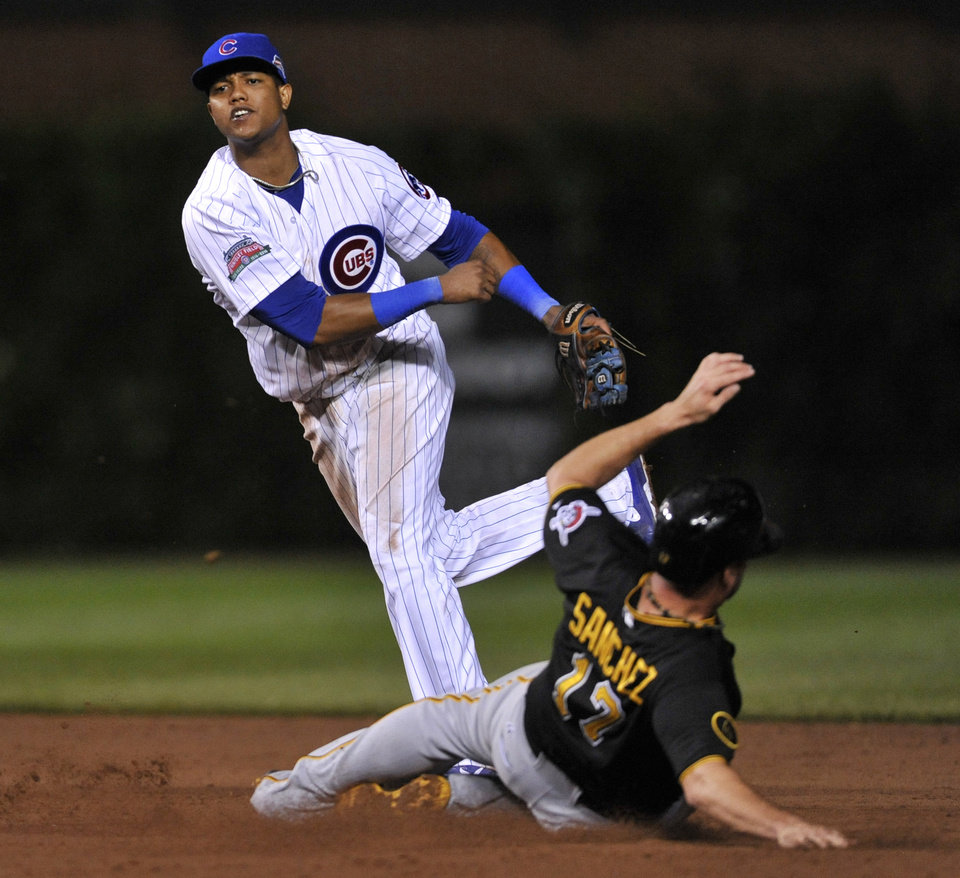 Photo - Chicago Cubs shortstop Starlin Castro throws to first base after forcing out Pittsburgh Pirates' Gaby Sanchez (17) at second base during the sixth inning of a baseball game in Chicago, Saturday, June 21, 2014. Jordy Mercer was out at first. (AP Photo/Paul Beaty)