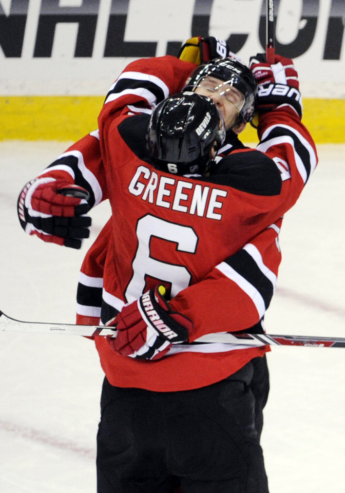 Photo - New Jersey Devils' Andy Greene (6) and Patrik Elias celebrates Greene's goal during the overtime period of an NHL hockey game Thursday, March 20, 2014, in Newark, N.J. The Devils won 4-3. (AP Photo/Bill Kostroun)