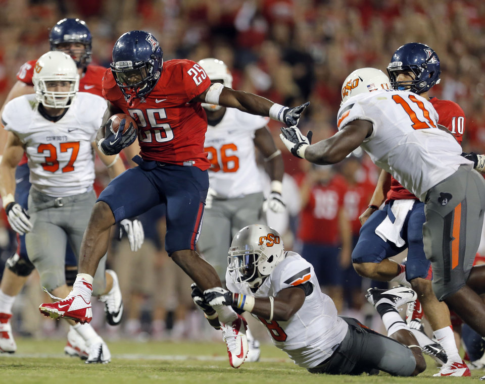 Arizona's Ka'Deem Carey (25) scores a touchdown as Oklahoma State's Daytawion Lowe (8) and Shaun Lewis (11) defend during the college football game between the University  of Arizona and Oklahoma State University at Arizona Stadium in Tucson, Ariz.,  Sunday, Sept. 9, 2012. Photo by Sarah Phipps, The Oklahoman