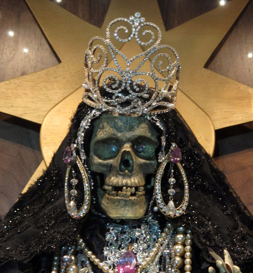 In this Feb. 12, 2013 photo, a statue of La Sante Muerte from an altar run by Arely Vazquez Gonzalez, a Mexican immigrant and transgender woman, is shown at inside a Queens, NY apartment. La Santa Muerte, an underworld saint most recently associated with the violent drug trade in Mexico, now is spreading throughout the U.S. among a new group of followers ranging from immigrant small business owners to artists and gay activists. In addition to showing up at drug crime scenes, the once-underground icon has been spotted on passion candles in Richmond, Va. grocery stores. The folk saint\'s image can be seen inside New York City apartments, in Minneapolis religious shops and during art shows in Tucson, Ariz. (AP Photo/Russell Contreras)
