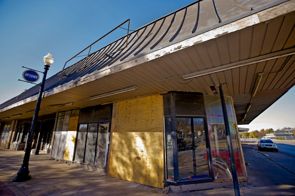 Photo -  Developer Johnathan Russell bought the shopping center at the corner of NW 23 and Walker Avenue unaware that historic facades were hidden under awnings and brick added over the past 40 years. The awning shown in this 2013 photo hid an engraved granite facade.   CHRIS LANDSBERGER -  CHRIS LANDSBERGER