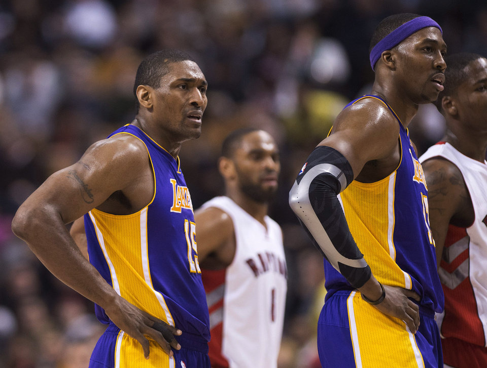Los Angeles Lakers forward Dwight Howard, right, looks at the referees with teammate Metta World Peace, left, after being ejected from the game while playing against the Toronto Raptors during first half NBA basketball action in Toronto on Sunday Jan. 20, 2013. (AP Photo/THE CANADIAN PRESS,Nathan Denette)
