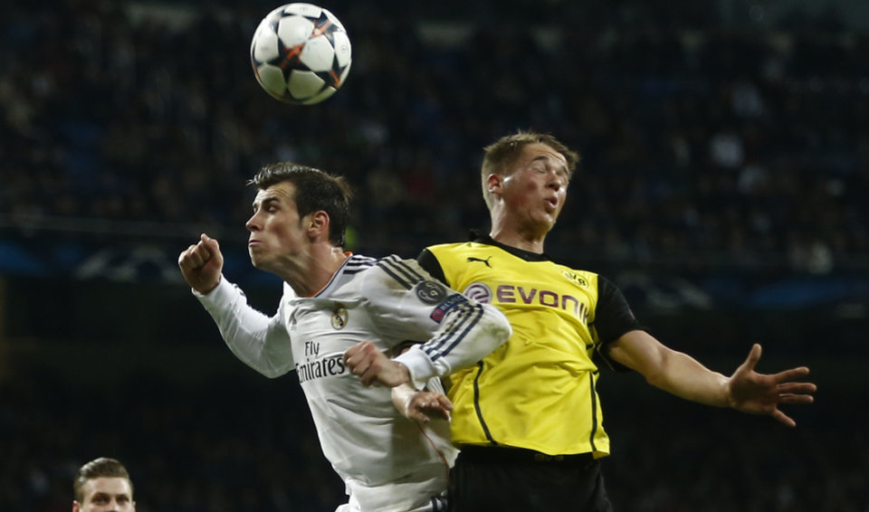 Photo - Real's Gareth Bale, left, and Dortmund's Erik Durm go for a header during a Champions League quarterfinal first leg soccer match between Real Madrid and Borussia Dortmund at the Santiago Bernabeu   stadium in Madrid, Spain, Wednesday, April 2, 2014. (AP Photo/Andres Kudacki)