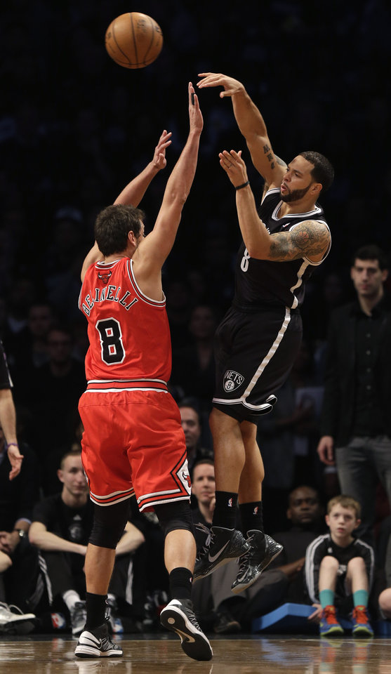 Photo - Brooklyn Nets' Deron Williams, right, passes the ball over Chicago Bulls' Marco Belinelli during the second quarter of Game 1 in the first round of the NBA basketball playoffs at the Barclays Center, Saturday, April 20, 2013 in New York. (AP Photo/Seth Wenig