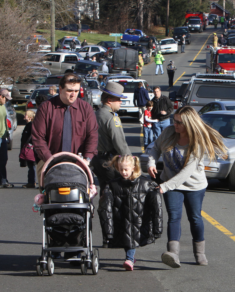 Photo - Parents walk away from the Sandy Hook School with their children following a shooting at the school Friday, Dec. 14, 2012 in Newtown, Conn. A man opened fire inside the Connecticut elementary school where his mother worked Friday, killing 26 people, including 18 children, and forcing students to cower in classrooms and then flee with the help of teachers and police. (AP Photo/The Journal News, Frank Becerra Jr.) MANDATORY CREDIT, NYC OUT, NO SALES, ONLINE OUT, TV OUT, NEWSDAY OUT; MAGS OUT ORG XMIT: NYWHI105