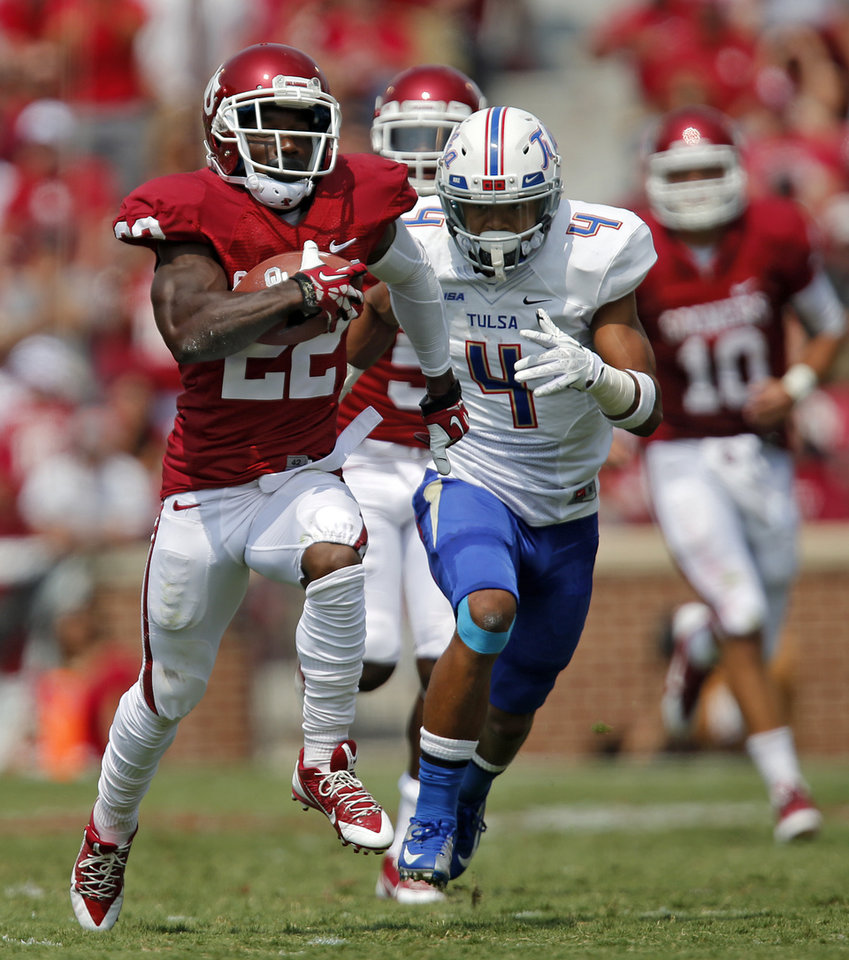 Oklahoma's Roy Finch (22) runs past Tulsa 's Darnell Walker (4) during the college football game between the University of Oklahoma Sooners (OU) and the University of Tulsa Hurricanes (TU) at the Gaylord-Family Oklahoma Memorial Stadium on Saturday, Sept. 14, 2013 in Norman, Okla.  Photo by Chris Landsberger, The Oklahoman