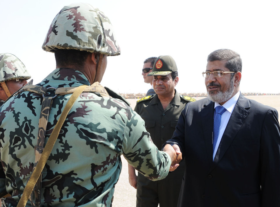 In this image released by the Egyptian Presidency, Egyptian President Mohammed Morsi, shakes hands with an Egyptian military soldier at a military base in Ismailia, Egypt, Wednesday, Oct. 10, 2012. Egyptian Minister of Defense, Lt. Gen. Abdel-Fattah el-Sissi is seen, second right. (AP Photo/Egyptian Presidency)