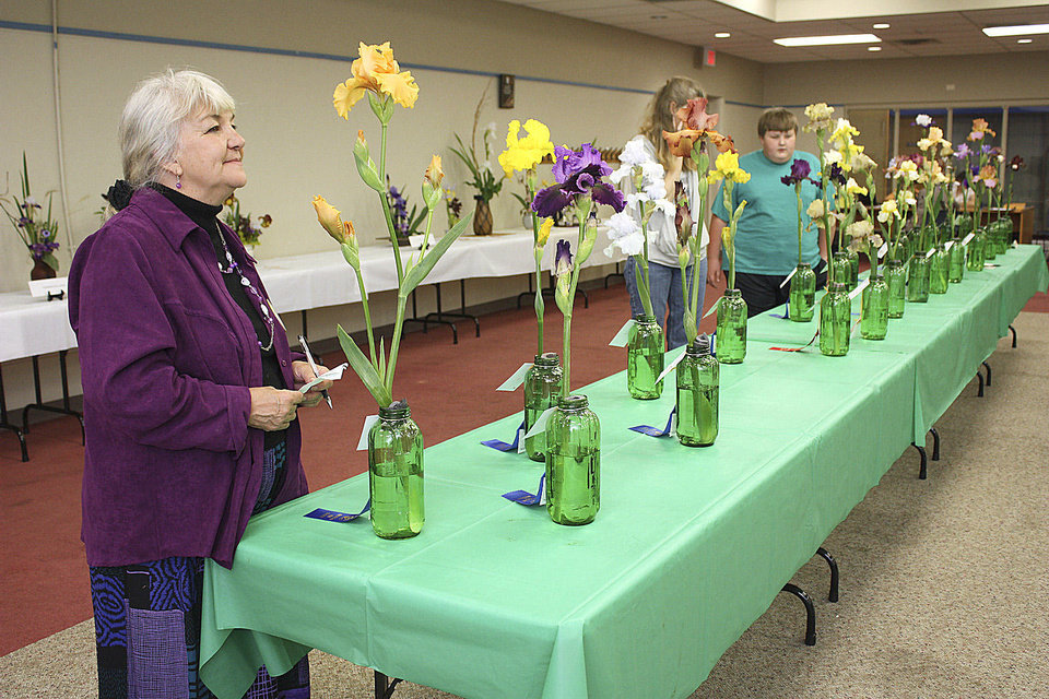Photo - Jackie Cortez, in the foreground, admires the display of entries at the Norman chapter's National Iris Society show. PHOTO BY LYNETTE LOBBAN, FOR THE OKLAHOMAN