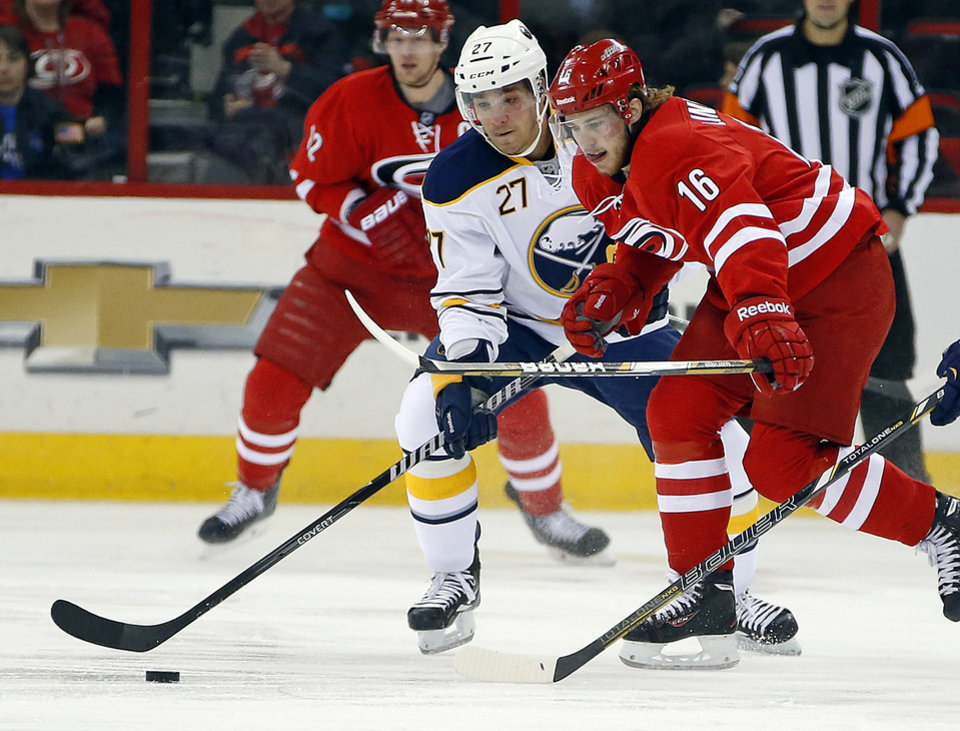 Photo - Carolina Hurricanes' Elias Lindholm (16), of Sweden, battles Buffalo Sabres' Matt D'Agostini (27) for the puck during the first period of an NHL hockey game in Raleigh, N.C., Thursday, March 13, 2014. (AP Photo/Karl B DeBlaker)