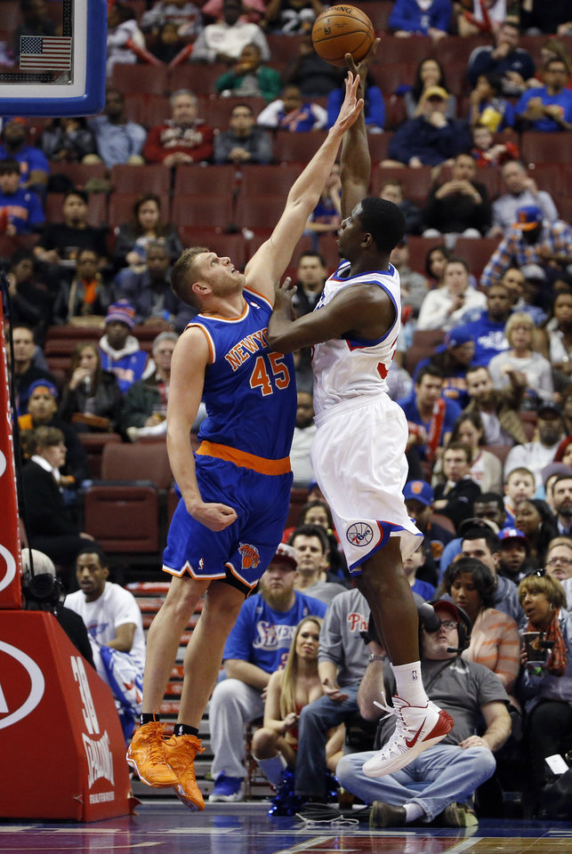 Photo - Philadelphia 76ers' Henry Sims, right, goes up for a shot against New York Knicks' Cole Aldrich during the first half of an NBA basketball game, Friday, March 21, 2014, in Philadelphia. (AP Photo/Matt Slocum)