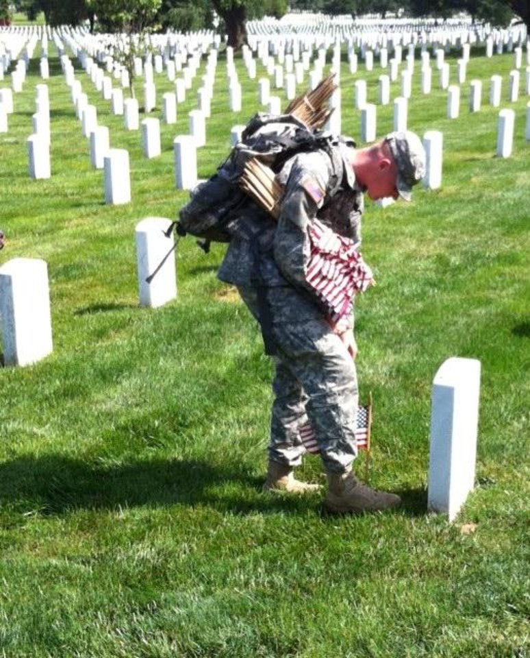 Soldiers place memorial day flags at Arlington Cemetery