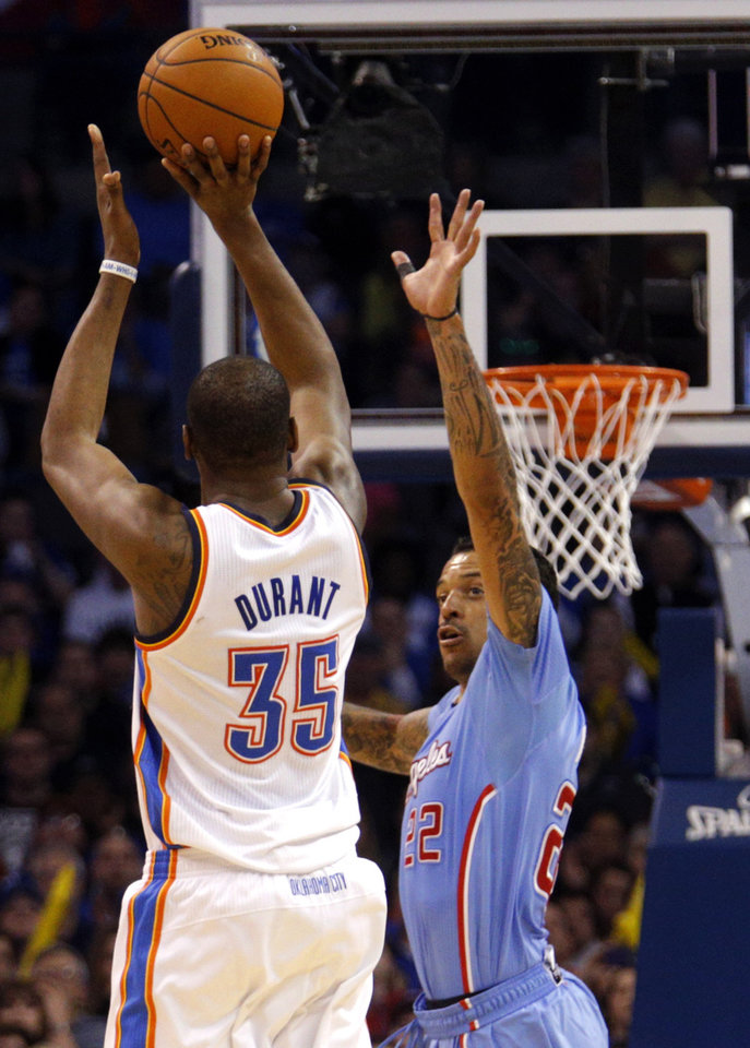 Photo - Oklahoma City 's Kevin Durant (35) ties for a three-point shot as Los Angeles' Matt Barnes (22) defends during the NBA game between the Oklahoma City Thunder and the Los  Angeles Clippers at the Chesapeake Energy Arena, Sunday, Feb. 23, 2014. Photo by Sarah Phipps, The Oklahoman