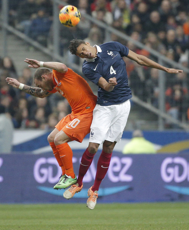 Photo - Raphael Varane of France, right, and Netherlands' Wesley Sneijder jump for the ball during the international friendly match between France and Netherlands at the Stade de France stadium, outside Paris, Wednesday, March 5, 2014. (AP Photo/Christophe Ena)